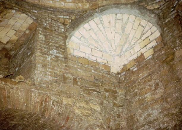 Baptisterio de Gabia Grande: Detalle de una de las trompas que soportan la bóveda y parte del arco del ábside y la ventana de ese muro
