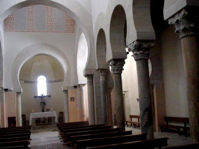 Vista interior de la basílica. Naves central y norte y ábside principal. Observar la separación de las naves mediante arcos de herradura sobre columnas y capiteles.