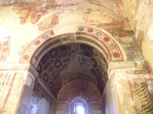 Vista de la decoración del ábside sur.Detalle del arco de acceso, de medio punto sobre pilares e impostas y de la bóveda de cañón sobre una imposta corrida.