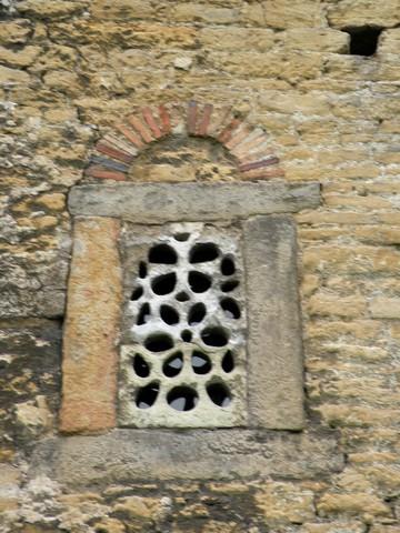 Ventana con celosía del testero en el ábside norte. Rectangular, adintelada y con arco de descarga de medio punto en ladrillo, forma habitual en la arquitectura asturiana.